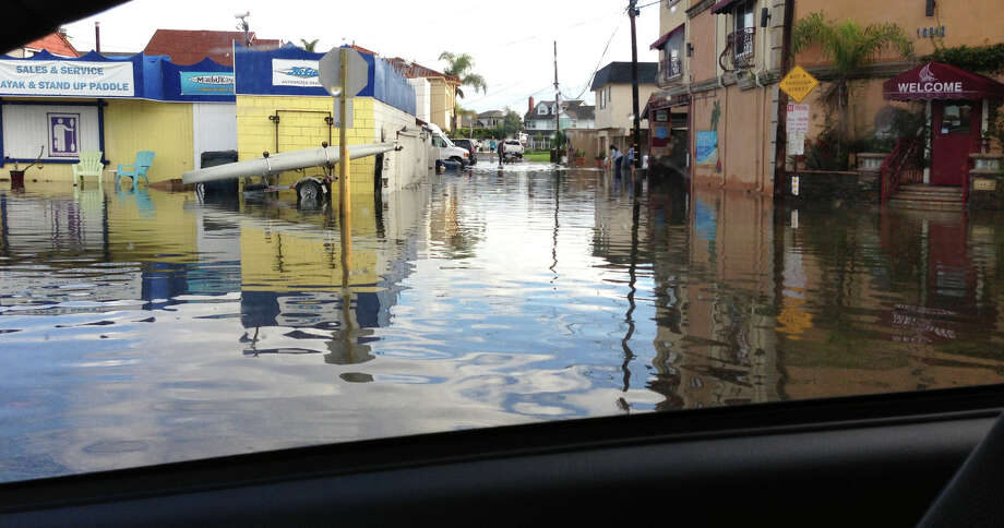 This image provided by Jon Tuico shows a flooded street in the Sunset Beach area of Huntington Beach, Calif., Thursday Dec. 13, 2012.  High tides have caused minor street flooding in some low-lying areas along the Southern California coast. Photo: Jon Tuico, Associated Press / Jon Tuico