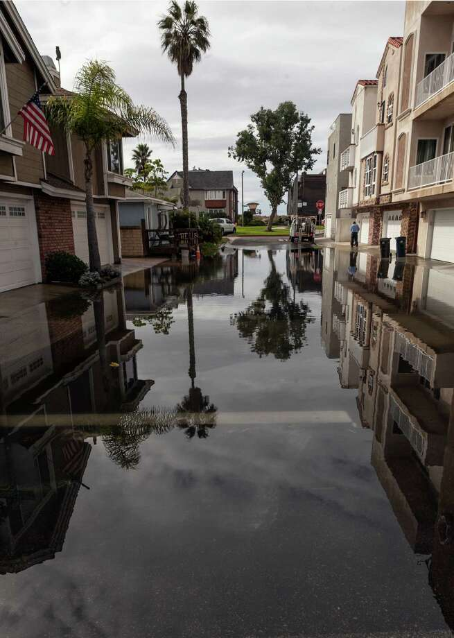 An overflowed street adjacent to Pacific Coast Highway  is seen in the Sunset Beach area of Huntington Beach, Calif., Thursday, Dec. 13, 2012. Astronomical high tides have caused minor street flooding in some low-lying areas along the Southern California coast. Photo: Damian Dovarganes, Associated Press / AP