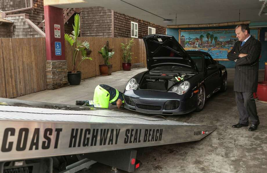 PowerTurbine president Fred Grether has his Porsche Sports car towed away after flood waters damaged its electric systems near the overflowed streets onto Pacific Coast Highway in the Sunset Beach area of Huntington Beach, Calif., Thursday, Dec. 13, 2012. Astronomical high tides have caused minor street flooding in some low-lying areas along the Southern California coast. Photo: Damian Dovarganes, Associated Press / AP