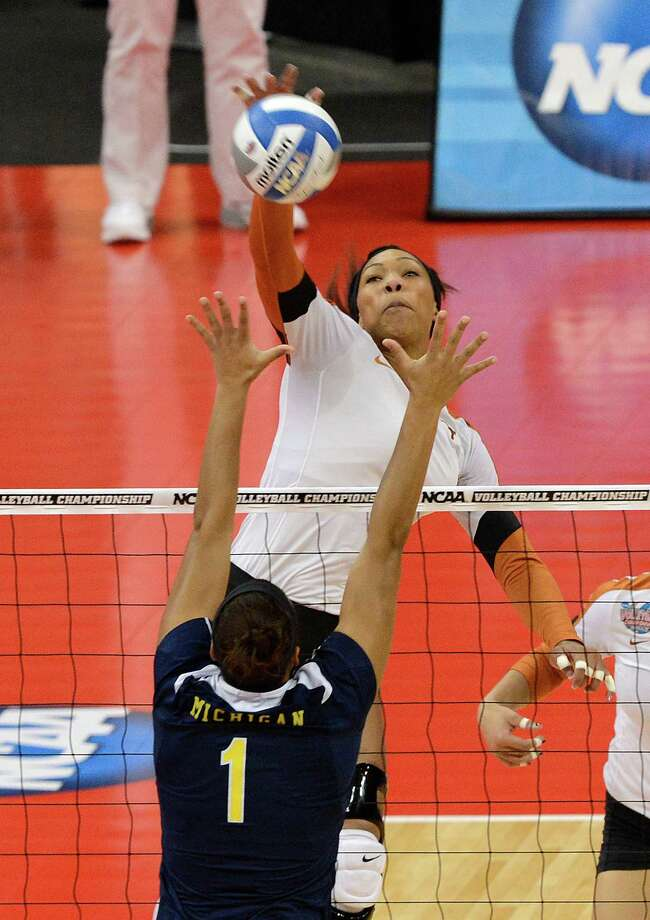 Texas' Khat Bell, rear, spikes the ball through the defense of Michigan's Molly Toon during the national semifinals of the NCAA college women's volleyball tournament Thursday, Dec. 13, 2012 in Louisville, Ky. (AP Photo/Timothy D. Easley) Photo: Timothy D. Easley, Associated Press / FR43398 AP