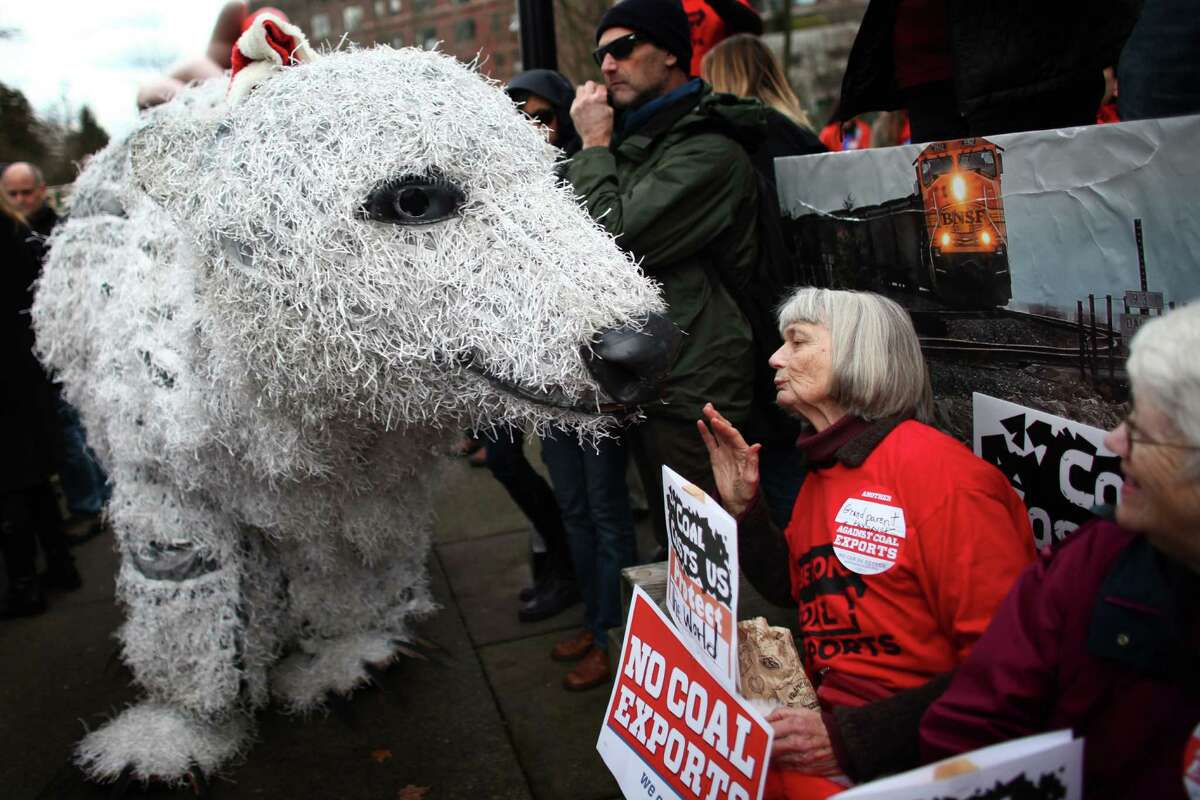 Pat Holm of Olympia is visited by a polar bear puppet during a rally before a Cherry Point coal export terminal scoping meeting. The proposed terminal would be one of the shipping points for U.S. coal over the Pacific to Asia. The meeting was held on Thursday, December 13, 2012 at the Washington State Convention Center, and offered citizens a chance to give input on an upcoming environmental impact study and statement.