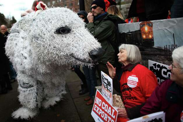Pat Holm of Olympia is visited by a polar bear puppet during a rally before a Cherry Point coal export terminal scoping meeting. The proposed terminal would be one of the shipping points for U.S. coal over the Pacific to Asia. The meeting was held on Thursday, December 13, 2012 at the Washington State Convention Center, and offered citizens a chance to give input on an upcoming environmental impact study and statement. Photo: JOSHUA TRUJILLO / SEATTLEPI.COM
