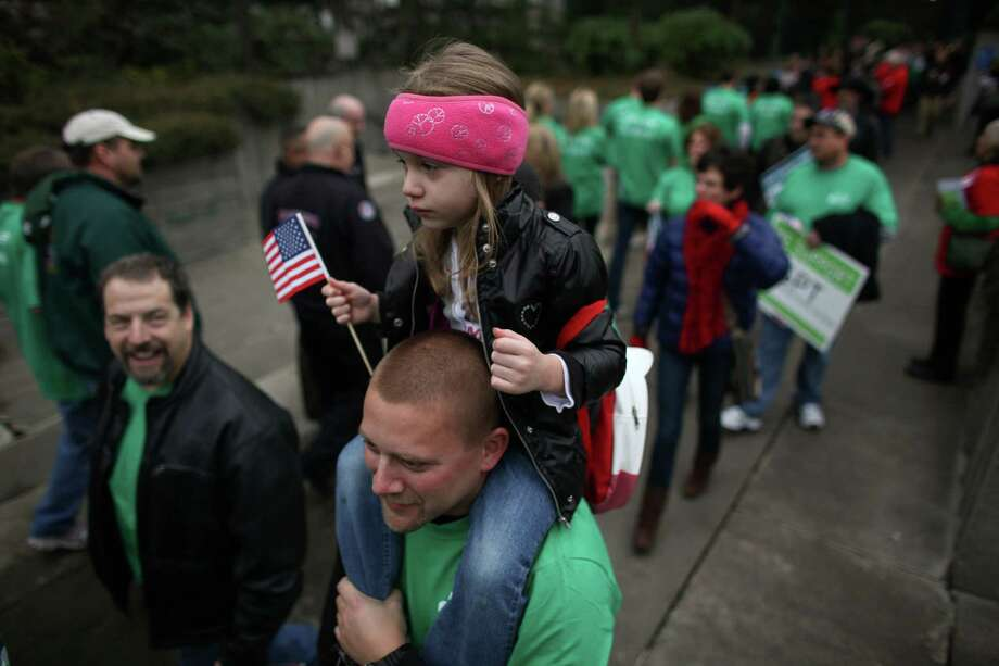 Joseph Vavrina of West Seattle and his daughter Jolee, 4, wait in line to offer support for the proposed Gateway Pacific Terminal during a scoping meeting about the proposed Cherry Point coal export terminal in Whatcom County. Photo: JOSHUA TRUJILLO / SEATTLEPI.COM