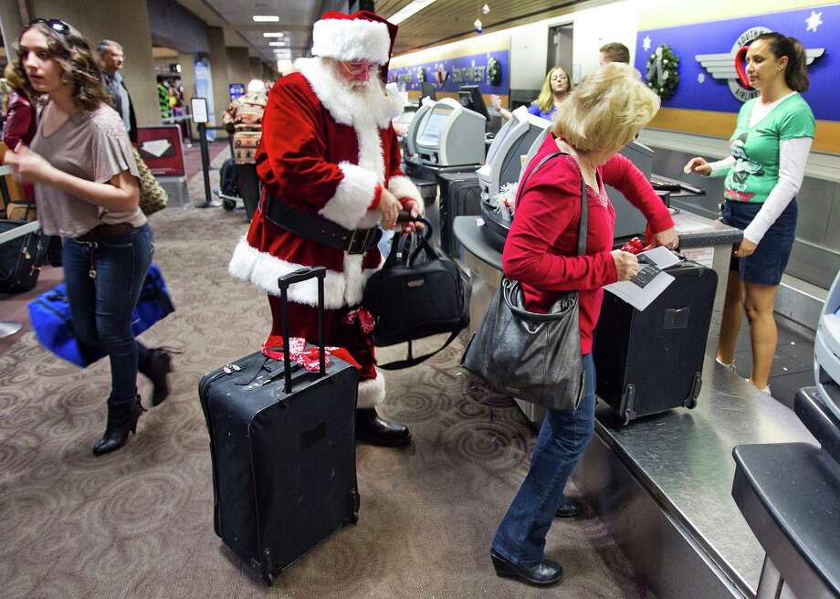 FILE - In this Wednesday, 21, 2011, file photo, holiday travelers, including Donald Occimio of Mesa, Ariz., dressed as Santa Claus, and his wife Diane check in with customer service agent Angelee Arciniega, right, for their Southwest Airlines flight at the Terminal 4 ticketing area at Sky Harbor International Airport, in Phoenix. The 2012 Christmas travel season could be the busiest in six years, with AAA predicting that 93.3 million Americans will hit the road. That's 1.6 percent more than last year and just 400,000 people shy of the 2006 record.  (AP Photo/The Arizona Republic, Tom Tingle)  MARICOPA COUNTY OUT; MAGS OUT; NO SALES Photo: Tom Tingle