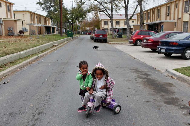 Wheatley Courts residents Shanyce Murray, 5, right, plays with her sister, Jayla Murray, 2, outside their apartment in San Antonio on Thursday, Dec. 13, 2012. The neighborhood will undergo a major renovation with the award of a $29.7 million grant from the U.S. Department of Housing and Urban Development which was announced Thursday. The siblings have lived with their parents and three other siblings for three years at the apartment complex in a three bedroom apartment. Photo: Lisa Krantz, San Antonio Express-News / © 2012 San Antonio Express-News