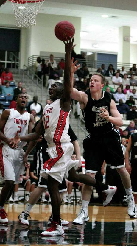 Travis forward Juwan Williams, center, throws up a shot as Archbishop Mitty forward Branson Farrell trails on defense in the first half Thursday night. Photo: Billy Smith II, Staff / © 2013 Houston Chronicle