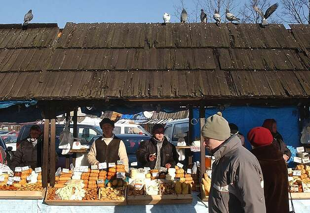FILE - In this Jan. 14, 2006 file photo, tourists walk past street vendors offering regional smoked cheese 'oscypek'  in Zakopane, Poland. Little Miss Muffet could have been separating her curds and whey from the sixth millennium B.C., according to a new study that finds the earliest solid evidence of cheese-making. Scientists performed a chemical analysis on fragments from 34 pottery sieves discovered in Poland to determine what they were used for. Until now, experts weren't sure whether such sieves were used to make cheese, beer or honey. (AP Photo/Czarek Sokolowski, File) Photo: Czarek Sokolowski, Associated Press