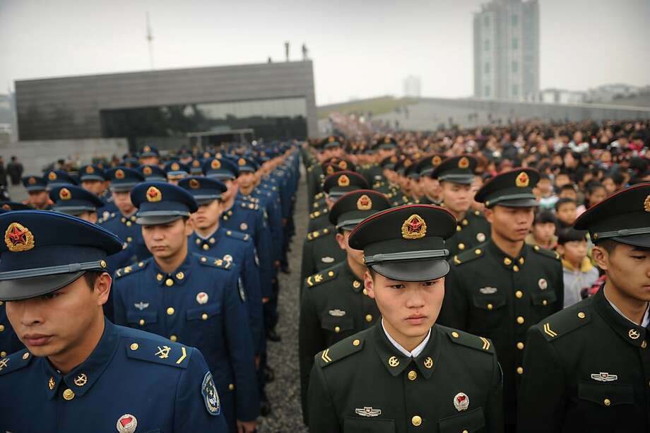 Chinese military personnel attend a a ceremony for victims on the 75th anniversary of the Nanjing massacre at the Memorial Museum in Nanjing on December 13, 2012.  Air raid sirens sounded in the Chinese city of Nanjing on December 13 as it marked the 75th anniversary of the mass killing and rape committed there by Japanese soldiers -- with the Asian powers' ties at a deep low. Photo: Peter Parks, AFP/Getty Images