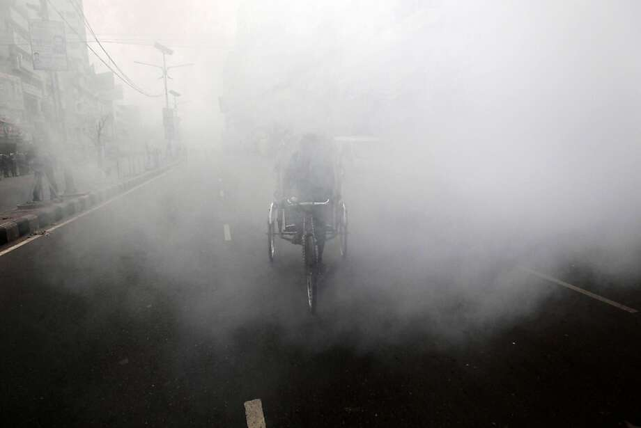 A Bangladeshi rickshaw puller pedals past a cloud of a smoke after a homemade bomb exploded during a nationwide half-day strike in Dhaka, Bangladesh, Thursday, Dec. 13, 2012. Homemade bombs exploded in Bangladesh's capital and police fired tear gas at demonstrators as opposition parties enforced a general strike on Thursday, demanding that the government restore an election-time caretaker administration. Photo: A.M. Ahad, Associated Press