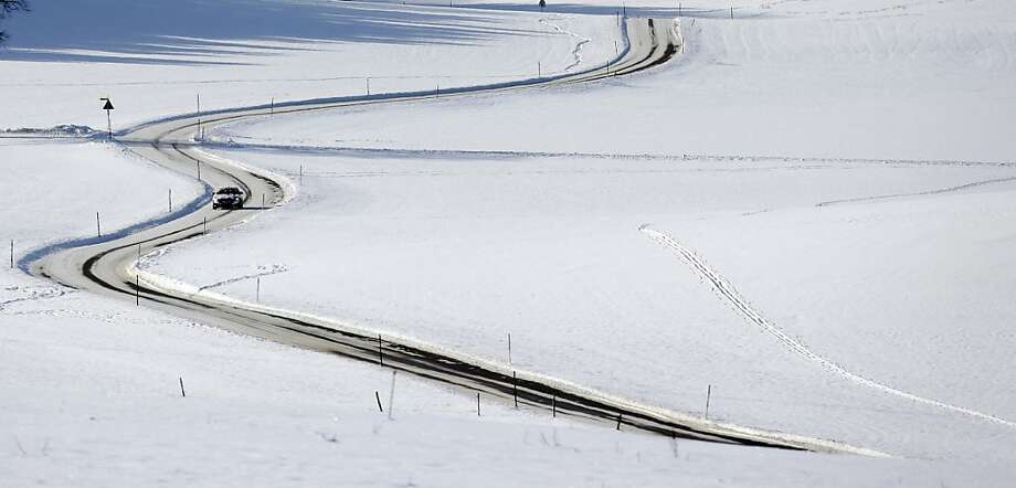 A car drives through a snow covered landscape near Starnberg, southern Germany, Thursday, Dec. 13, 2012. Weather forecasts predict changeable weather with rising temperatures for Germany during the coming days. Photo: Matthias Schrader, Associated Press