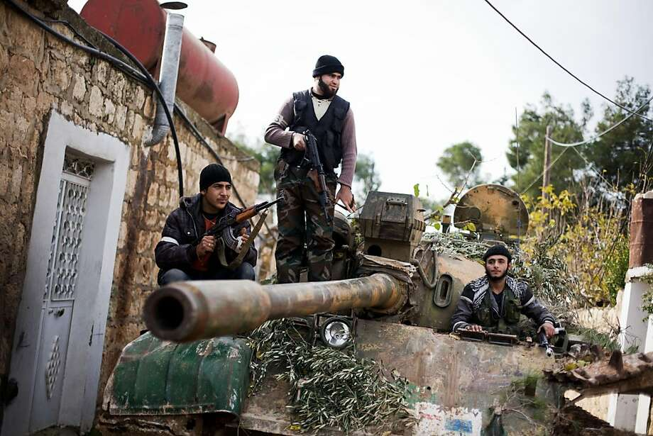 Kurdish members of the FSA are seen on a tank stolen from the Syrian Army in Fafeen village, north of Aleppo province, Syria, Wednesday, Dec 12, 2012. Photo: Manu Brabo, Associated Press