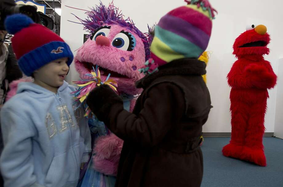 "Allisson Zuniga, 4, of College Park, Md., left, and Nahomy Arias, 4, of Hyattsville, Md., visit with Sesame Street character Abby Cadabby, as Elmo stands in the background, Thursday, Dec. 13, 2012, at the National Children's Museum in Oxon Hill, Md., during a preview of the museum's new location that features characters and activities from ""Sesame Street."" Photo: Jacquelyn Martin, Associated Press"