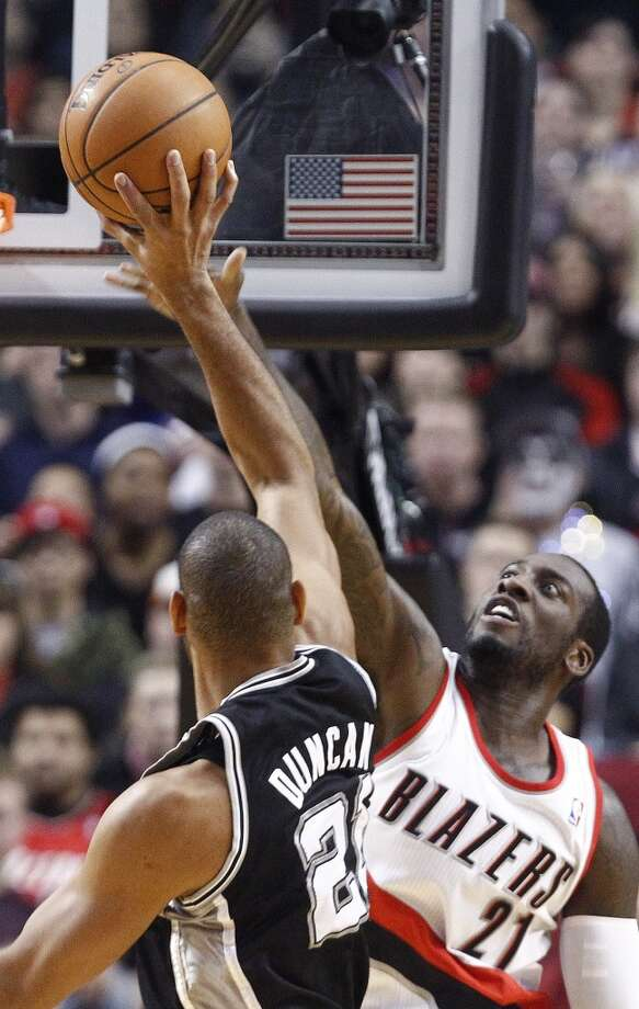 Portland Trail Blazers center J.J. Hickson, right, stretches to block a shot by San Antonio Spurs forward Tim Duncan during the first quarter of an NBA basketball game in Portland, Ore., Thursday, Dec. 13, 2012. (AP Photo/Don Ryan) (Associated Press)