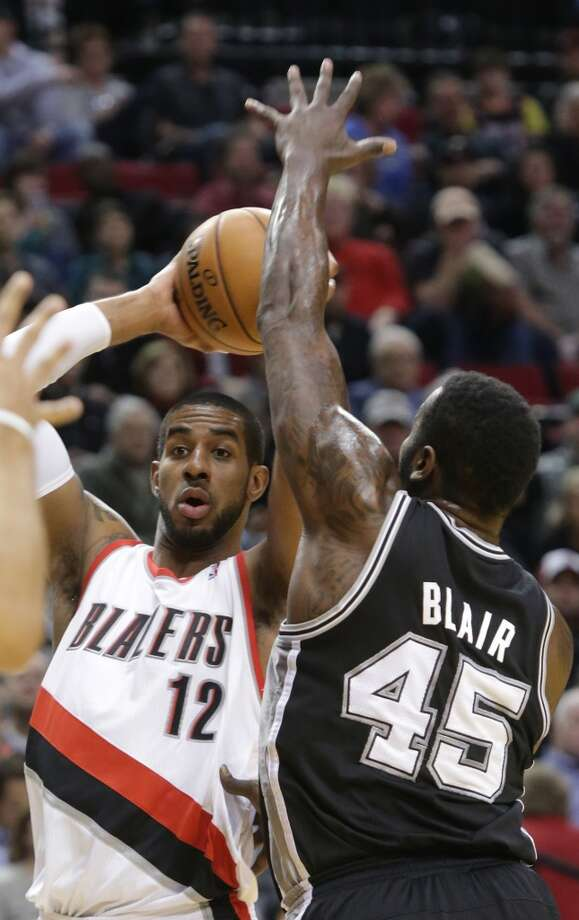 Portland Trail Blazers forward LaMarcus Aldridge, left, looks for help against defensive pressure from San Antonio Spurs center DeJuan Blair during the first quarter of an NBA basketball game in Portland, Ore., Thursday, Dec. 13, 2012.(AP Photo/Don Ryan) (Associated Press)