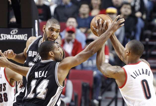 Portland Trail Blazers guard Damian Lillard, right, is double-teamed by the San Antonio Spurs' Gary Neal (14) and Tim Duncan during the first quarter of an NBA basketball game in Portland, Ore., Thursday, Dec. 13, 2012. (AP Photo/Don Ryan) (Associated Press)