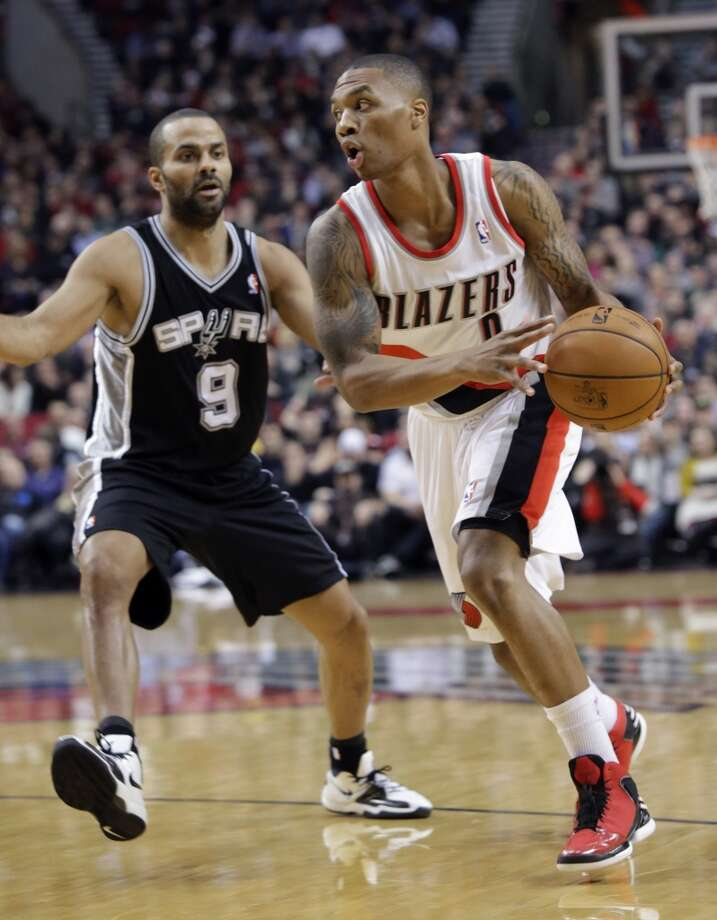 Portland Trail Blazers guard Damian Lillard, right, drives past San Antonio Spurs guard Tony Parker during the first quarter of an NBA basketball game in Portland, Ore., Thursday, Dec. 13, 2012. (AP Photo/Don Ryan) (Associated Press)