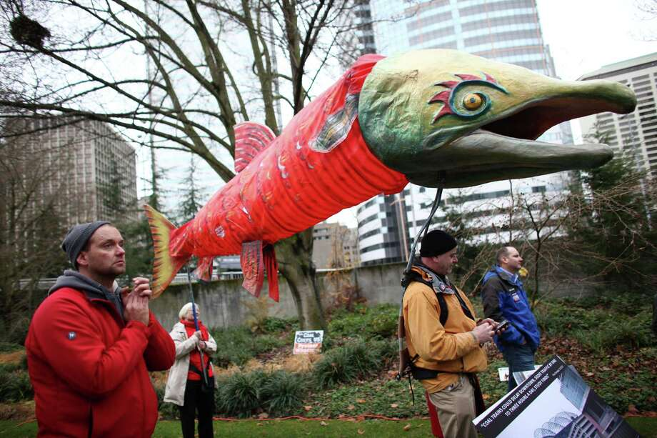 Alison Longley and Doug Skove hoist a salmon puppet as opponents gather in Freeway Park for a rally before a scoping meeting about the proposed Cherry Point coal export terminal in Whatcom County. Photo: JOSHUA TRUJILLO / SEATTLEPI.COM