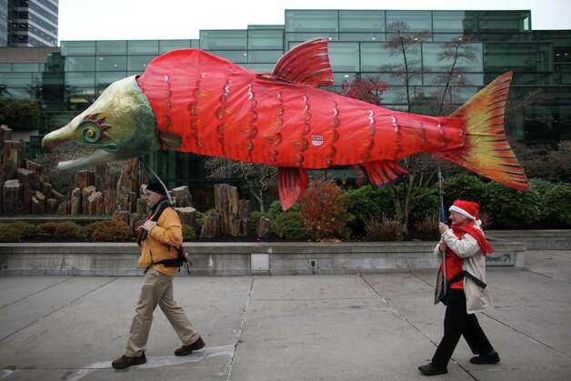 Doug Skove, left, and Alison Longley hoist a salmon puppet as opponents gather in Freeway Park for a rally before the scoping meeting. Photo: JOSHUA TRUJILLO / SEATTLEPI.COM