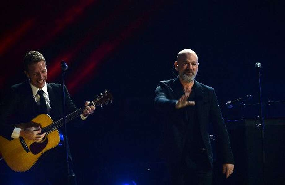 Chris Martin (L) performs as Michael Stipe (R) waves on stage during 12-12-12 ~ TheConcert For Sandy Relief December 12, 2012 at Madison Square Garden in New York. AFP PHOTO/DON EMMERTDON EMMERT/AFP/Getty Images