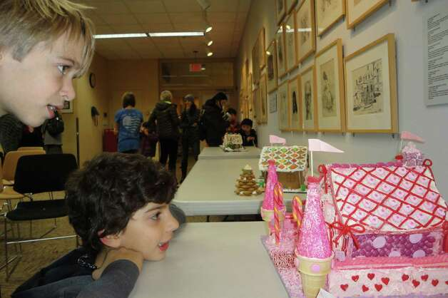 Charles Hulina, left, 10, and Spencer Henske, 9, both of Westport, admire the elaborate pink gingerbread palace created by the Dear family, also of Westport, for the gingerbread house decorating contest sponsored by the Westport-Weston Chamber of Commerce. The entries were displayed Thursday at the Westport Public Library.  Westport CT 12/13/12 Photo: Meg Barone / Westport News freelance