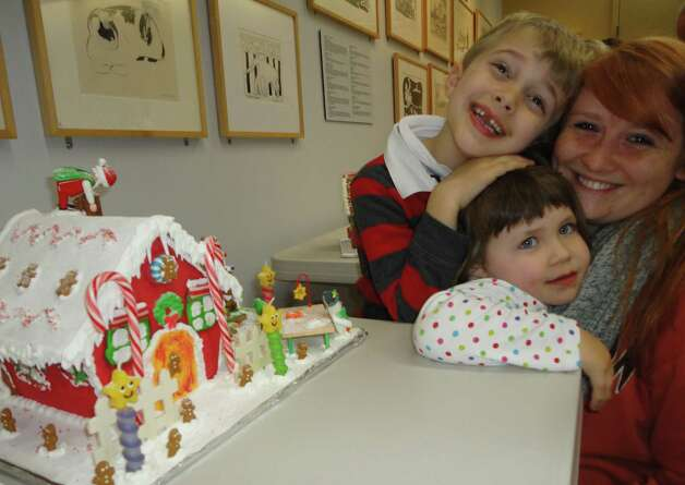Ben Grimm, 5, and his sister Isabella, 3, of Westport pose with their au pair Inna Potapov with their gingerbread house on display Thursday at the Westport Public Library. The three of them worked on their gingerbread house decorations for four afternoons after Ben got home from school.  Westport CT 12/13/12 Photo: Meg Barone / Westport News freelance