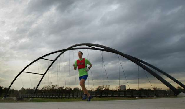 Clouds fill the morning sky as a runners makes his way down a running trail near the Bill Coats bridge Friday, Dec. 14, 2012, in Houston. Photo: Cody Duty, Houston Chronicle / © 2012 Houston Chronicle