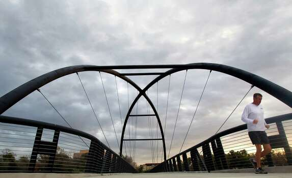 "Clouds fill the morning sky as Mike Kruger crosses the Bill Coats bridge Friday, Dec. 14, 2012, in Houston. ""It's perfect running weather,"" he said. Photo: Cody Duty, Houston Chronicle / © 2012 Houston Chronicle"