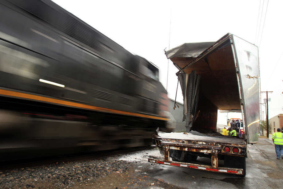 A locomotive (left) passes a trailer that was hit by a different train early Friday morning around 1:00 a.m. near Culebra and North San Marcos. Police said the driver of the truck parked too close to the tracks and fell asleep while waiting for his load of 45,000 pounds of flour to be unloaded. There were no injuries during the incident. Photo: JOHN DAVENPORT, San Antonio Express-News / ©San Antonio Express-News/Photo Can Be Sold to the Public