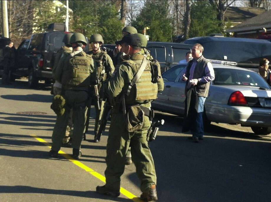 Swat team officers respond to a school shooting at Sandy Hook Elementary School in Newton, Conn. according to AP. At least 20 people have been killed according to AP, among them 10 children. Photo: Brian Koonz, News-Times