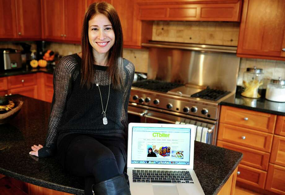 Stephanie Webster, founder of CTBites.com, a website devoted to food and restaurant reviews for Fairfield County, sits in her Westport kitchen with her site open beside her. Photo: Autumn Driscoll / Connecticut Post