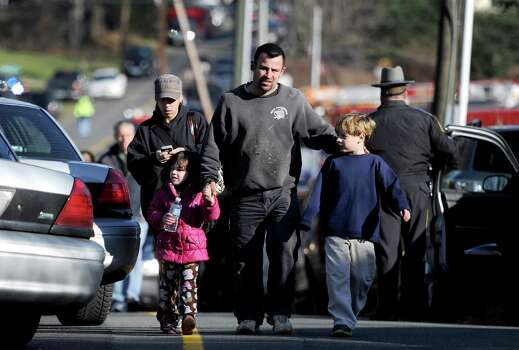 Parents leave a staging area after being reunited with their children following a shooting at the Sandy Hook Elementary School in Newtown, Conn., about 60 miles (96 kilometers) northeast of New York City, Friday, Dec. 14, 2012. An official with knowledge of Friday's shooting said 27 people were dead, including 18 children. It was the worst school shooting in the country's history. Photo: Jessica Hill / Associated Press
