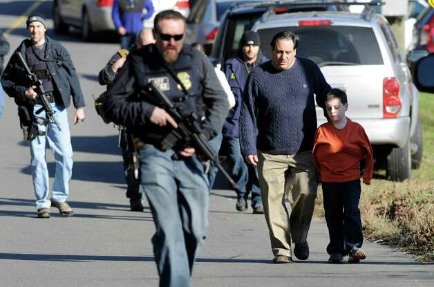 Parents leave a staging area after being reunited with their children following a shooting at the Sandy Hook Elementary School in Newtown, Conn., on Friday, Dec. 14, 2012. Photo: Associated Press