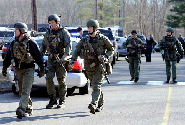 State Police are on scene following a shooting at the Sandy Hook Elementary School in Newtown, Conn., about 60 miles (96 kilometers) northeast of New York City, Friday, Dec. 14, 2012. An official with knowledge of Friday's shooting said 27 people were dead, including 18 children. (AP Photo/Jessica Hill) Photo: Associated Press