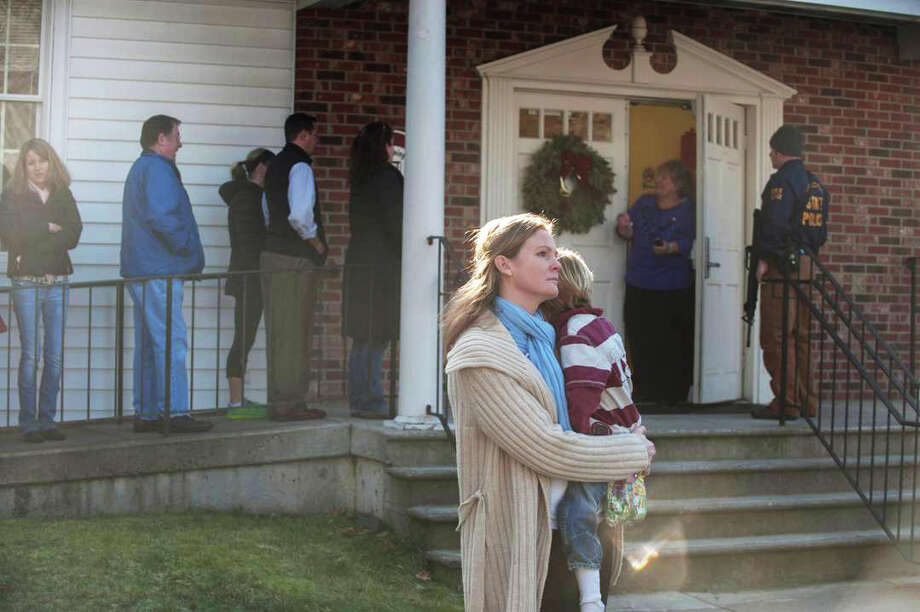 A woman holds her child outside a church near Sandy Hook Elementary School, where officials said 20-year-old Adam Lanza killed 26 people, including 20 children, as youngsters cowered in their classrooms and trembled helplessly at the sound of gunfire. Officials said Lanza, armed with two handguns, committed suicide. They said another person was found dead at a second scene, bringing the death toll to 28.  Photo: Douglas Healey, Getty Images / 2012 Getty Images