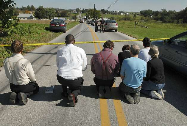 People kneel and pray on White Oak Road, Monday, Oct. 2, 2006, in Nickel Mines, Pa. A milk-truck driver carrying three guns and a childhood grudge stormed a one-room Amish schoolhouse Monday, sent the boys and adults outside, barricaded the doors with two-by-fours, and then opened fire on a dozen girls, killing three people before committing suicide. Photo: Dan Marschka, AP