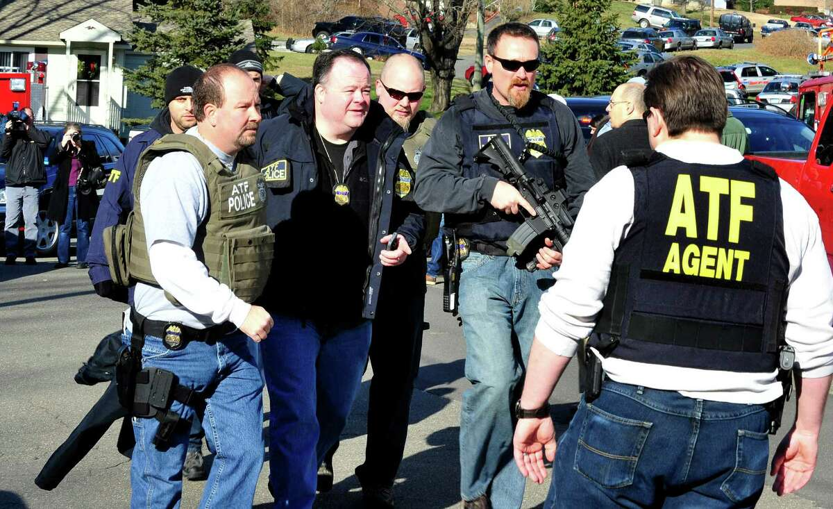 Armed federal agents approach Sandy Hook Elementary School in response to shootings that killed 20 children and six teachers on Friday, Dec. 14, 2012.