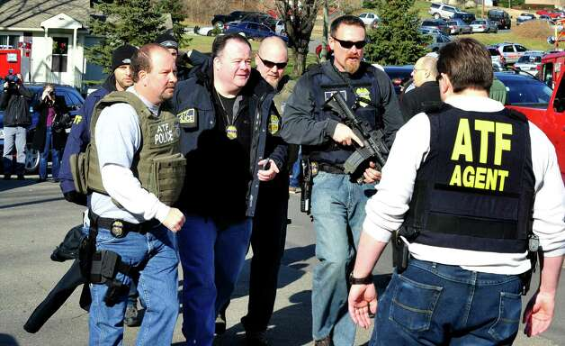 Armed federal agents approach Sandy Hook Elementary School in response to shootings that killed 20 children and six teachers on Friday, Dec. 14, 2012. Photo: Michael Duffy / The News-Times