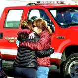Parents of Sandy Hook Elementary School students console each other outside the Sandy Hook Firehouse after shootings at the school Friday, Dec. 14, 2012.