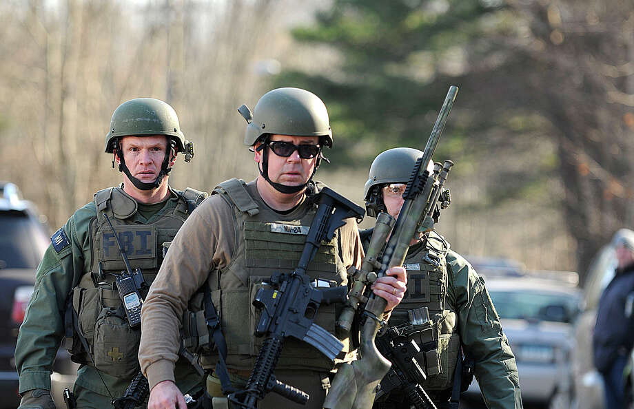 FBI SWAT team members walk along Dickinson Drive near Sandy Hook Elementary School in Newtown, Connecticut, Friday, December 14, 2012. Twenty-seven people, including 18 children, have been killed in a shooting at Sandy Hook Elementary School. (Cloe Poisson/Hartford Courant/MCT) Photo: Cloe Poisson, McClatchy-Tribune News Service / Hartford Courant