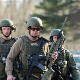 FBI SWAT team members walk along Dickinson Drive near Sandy Hook Elementary School in Newtown, Connecticut, Friday, December 14, 2012. Twenty-seven people, including 18 children, have been killed in a shooting at Sandy Hook Elementary School. (Cloe Poisson/Hartford Courant/MCT)