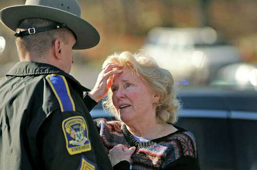 A woman talks to a state police officer at the scene of a shooting at Sandy Hook Elementary School in Newtown, Connecticut, Friday, December 14, 2012. Twenty-seven people, including 18 children, have been killed in a shooting at Sandy Hook Elementary School. (Cloe Poisson/Hartford Courant/MCT) Photo: Cloe Poisson, McClatchy-Tribune News Service / Hartford Courant