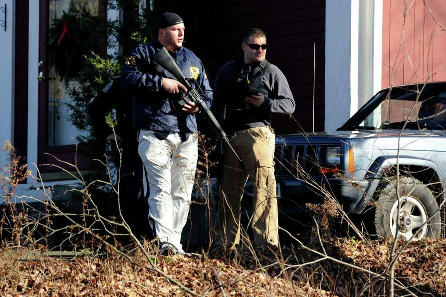 Law enforcement canvass an area following a shooting at the Sandy Hook Elementary School in Newtown,