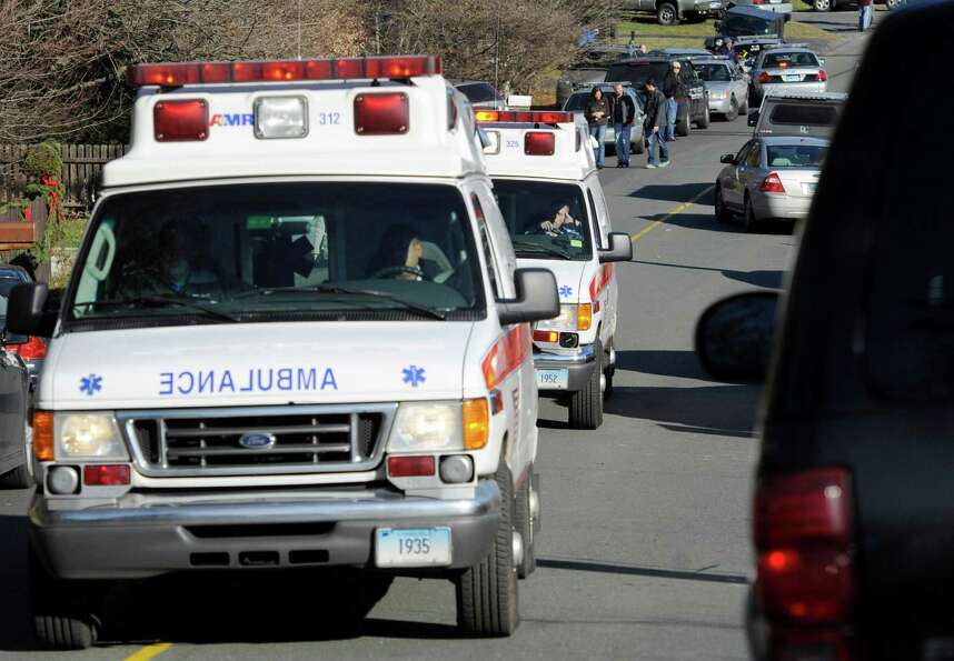 Ambulances leave an area near the scene of a shooting at the Sandy Hook Elementary School in Newtown