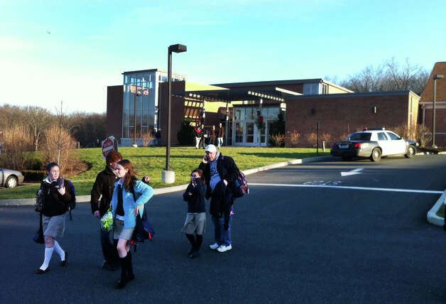 Students and parents leave Saint Rosa of Lima School  after a lockdown at that Newtown, Conn. facility on Friday, Dec. 14, 2012. Twenty-nine people including 22 children were massacred in a horrific bloodbath at the Sandy Hook Elementary School this morning, sources told the Associated Press. The gunman is dead, police said. Few other details were immediately available, and other reports contradicted those numbers. Photo: Christian Abraham / Connecticut Post