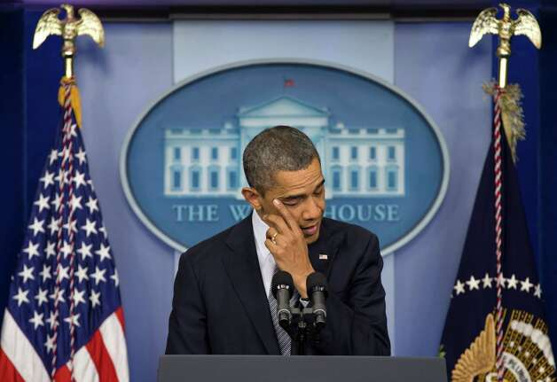 President Barack Obama wipes his eye as he talks about the Connecticut elementary school shooting, Friday, Dec. 14, 2012, in the White House briefing room in Washington. (AP Photo/Carolyn Kaster) Photo: Carolyn Kaster, Associated Press / AP