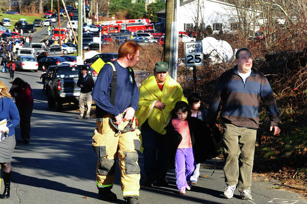 After a horrific shooting at Sandy Hook Elementary School nearby, parents and children are escorted from the Newtown Fire Department on Riverside Drive in Newtown, Conn. on Friday December 14, 2012. Photo: Christian Abraham / Connecticut Post