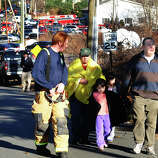After a horrific shooting at Sandy Hook Elementary School nearby, parents and children are escorted from the Newtown Fire Department on Riverside Drive in Newtown, Conn. on Friday December 14, 2012.