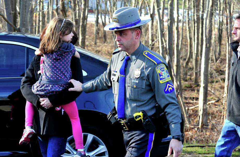 State Police escort a parent and Sandy Hook Elementary School student from the Sandy Hook Firehouse after shootings at the school on Friday, Dec. 14, 2012. Photo: Michael Duffy / The News-Times