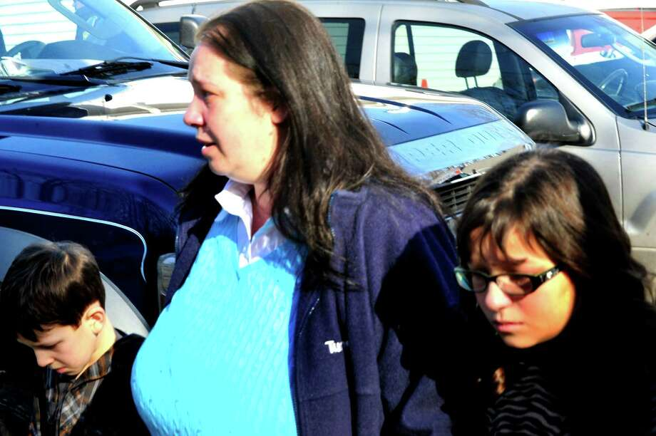 A parent escorts her Sandy Hook Elementary School students from the Sandy Hook Firehouse after shootings at the school on Friday, Dec. 14, 2012. Photo: Michael Duffy / The News-Times