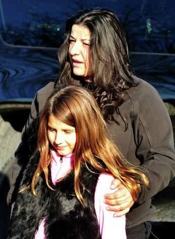 Alberta Bajraliu hugs her daughter, Venesa, 9, after shootings at the Sandy Hook Elementary School Friday, Dec. 14, 2012. Venesa was in her fourth grade art class at the time of the shootings. Photo: Michael Duffy / The News-Times